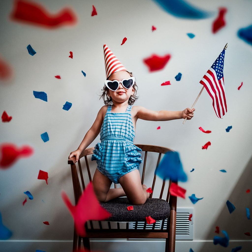 toddler girl waving flag surrounded by confetti